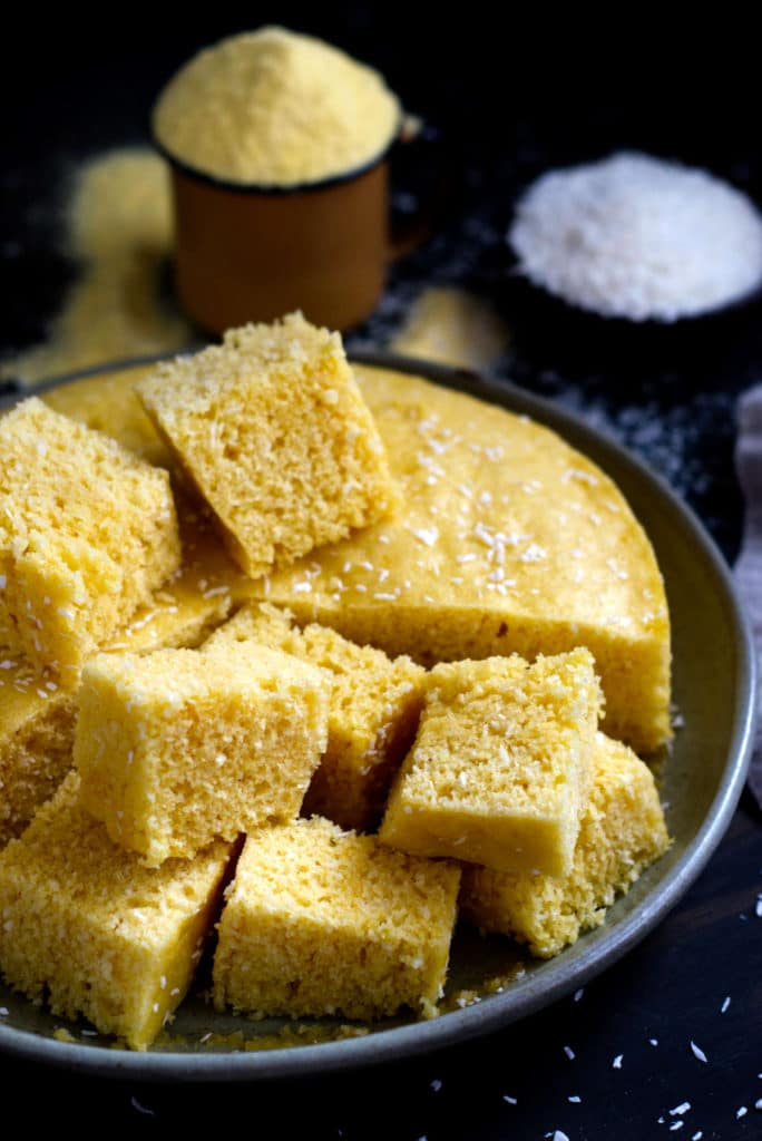 Steamed cornmeal and coconut cake cut in squares on a plate