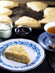 Scone made without butter in foreground, served over a white and blue place, a cup of tea besides and a baking sheet with fresh scones in the backgound